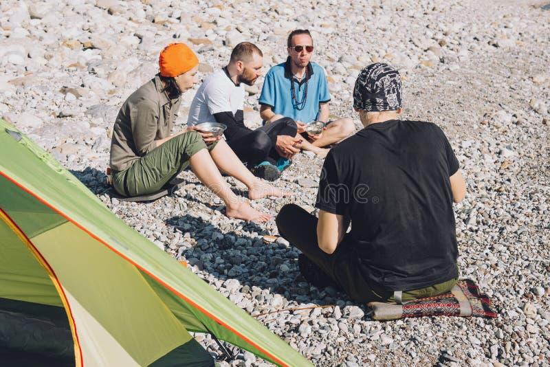 Szczęśliwi przyjaciele obozuje na plaży fotografia stock
