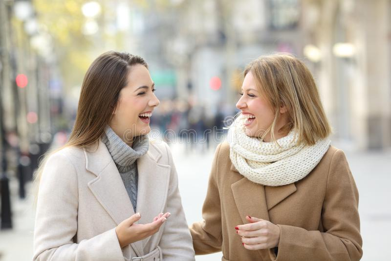 Szczęśliwi przyjaciele opowiada chodzić w ulicie w zimie obraz royalty free