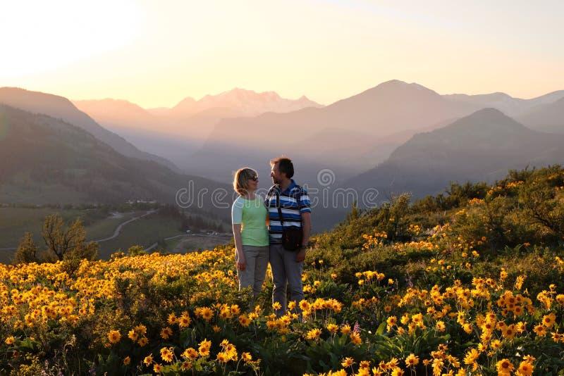 Szczęśliwi przyjaciele otaczający kwiatami obraz stock