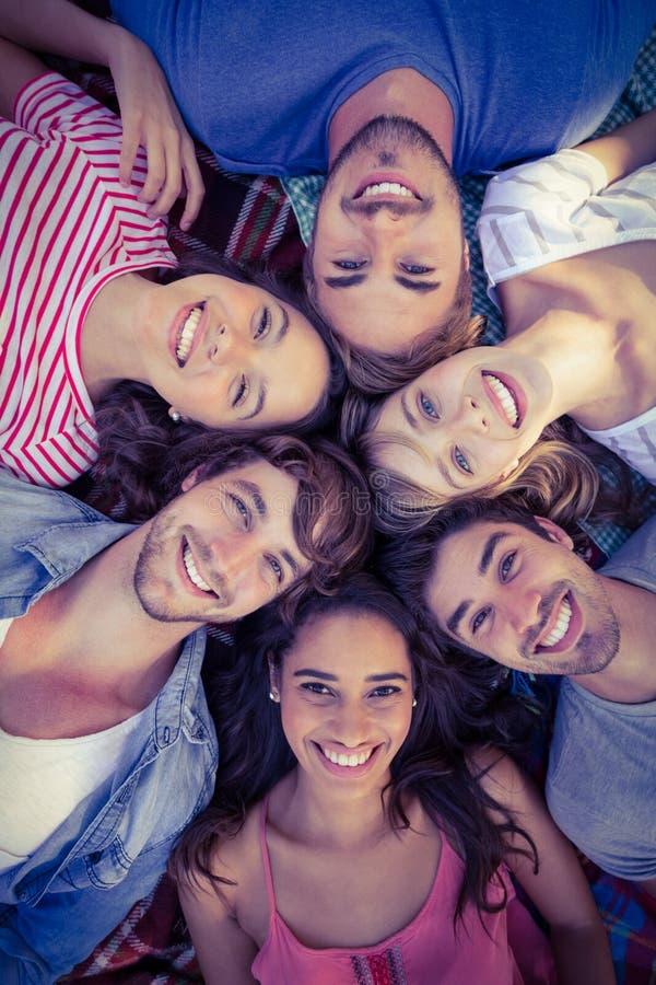 szczęśliwi przyjaciele skupia się w okręgu w parku zdjęcie stock