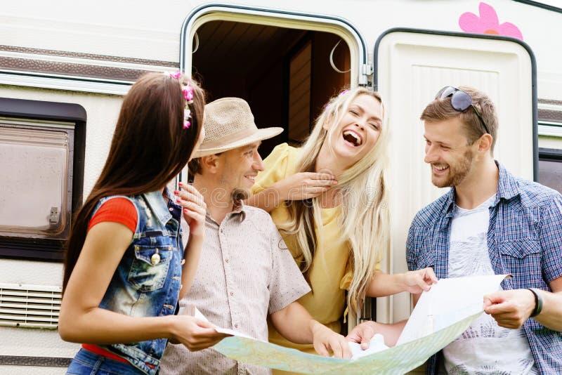 Szczęśliwi przyjaciele sprawdza planowanie i mapę ich trasa fotografia royalty free