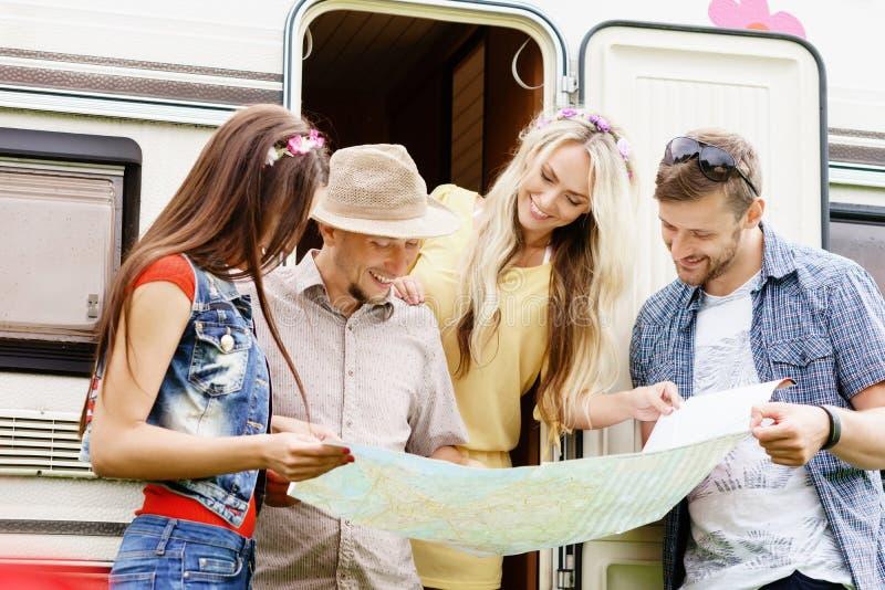 Szczęśliwi przyjaciele sprawdza planowanie i mapę ich trasa zdjęcia stock