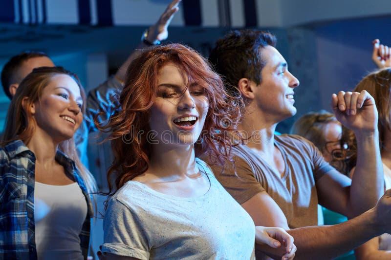 Szczęśliwi przyjaciele tanczy przy noc klubem obraz stock