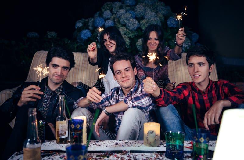 Szczęśliwi przyjaciele trzyma sparklers w przyjęciu obrazy stock