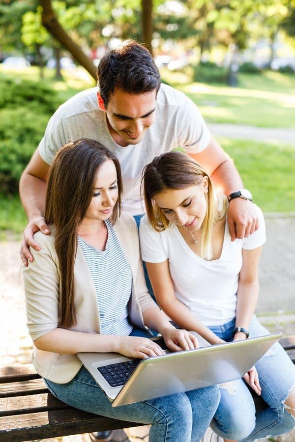 Szczęśliwi przyjaciele w parkowym używa ther laptopie, cieszyć się dzień i obrazy stock