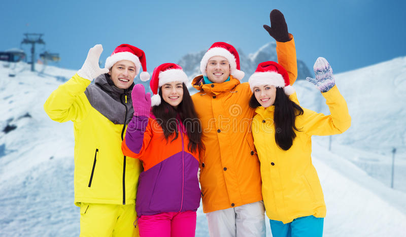 Szczęśliwi przyjaciele w Santa kapeluszach i narciarskich kostiumach outdoors zdjęcia stock