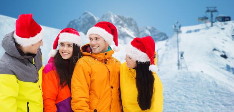 Szczęśliwi przyjaciele w Santa kapeluszach i narciarskich kostiumach outdoors zdjęcie royalty free