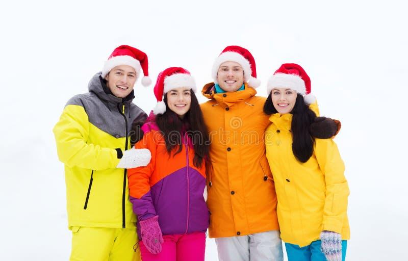 Szczęśliwi przyjaciele w Santa kapeluszach i narciarskich kostiumach outdoors zdjęcie stock