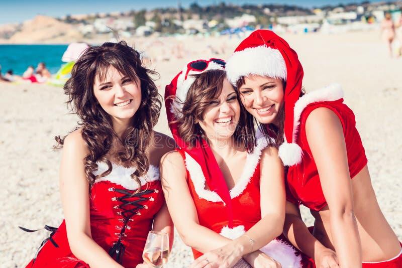 Szczęśliwi przyjaciele w Santa kapeluszach na plaży boże narodzenia łączący opróżniają szczególnie przemysłu internetów laptopu b zdjęcia stock