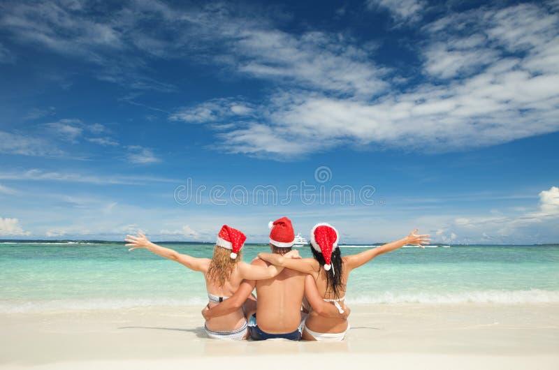 Przyjaciele w Santa kapeluszach na plaży. Boże Narodzenie wakacje obrazy stock