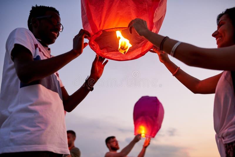 Szczęśliwi przyjaciele wszczyna niebo lampiony fotografia stock