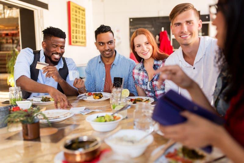 Szczęśliwi przyjaciele z pieniądze płaci rachunek przy restauracją fotografia stock