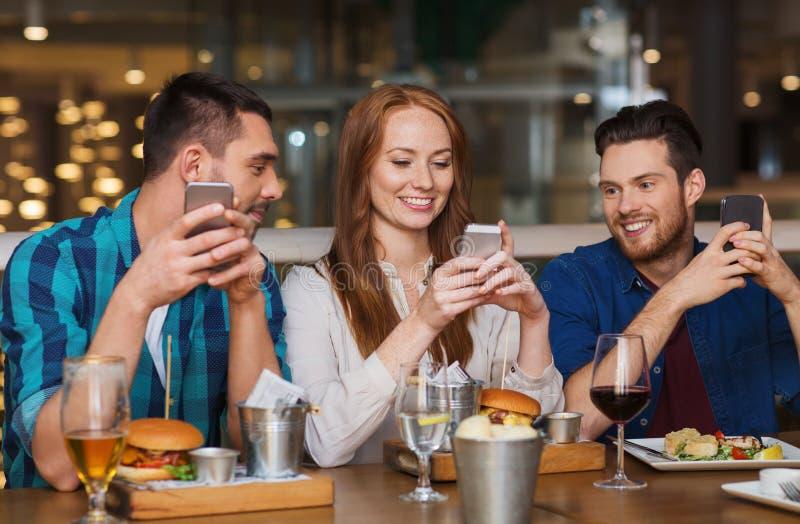Szczęśliwi przyjaciele z smartphones przy restauracją zdjęcia stock