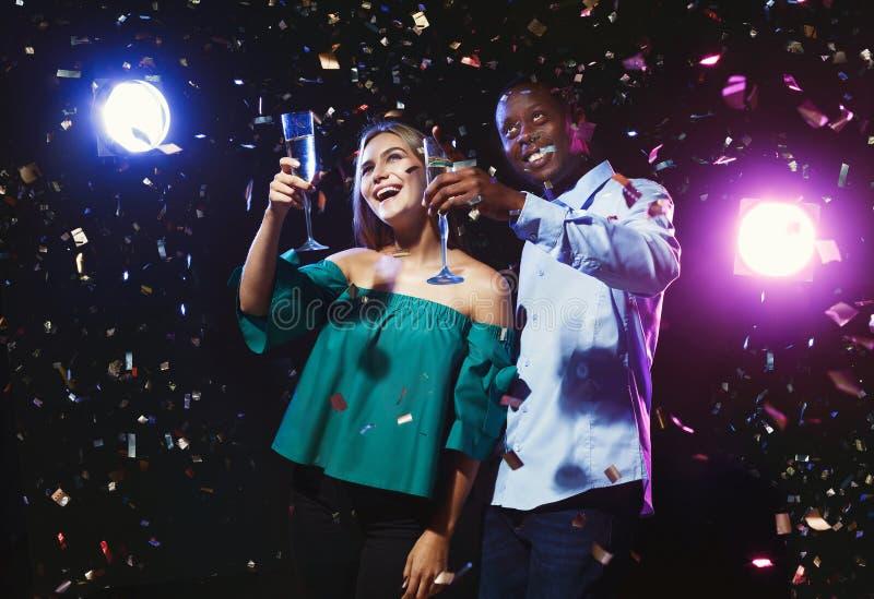 Szczęśliwi przyjaciele z szampańskimi fletami przy noc klubem bawją się obraz stock