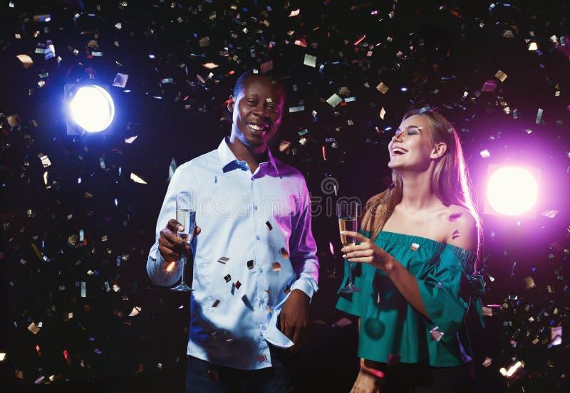 Szczęśliwi przyjaciele z szampańskimi fletami przy noc klubem bawją się zdjęcia stock