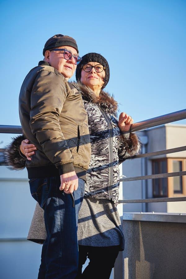 Szczęśliwi radośni seniory dobierają się ciepło ubierającą pozycję na balkonie obraz stock