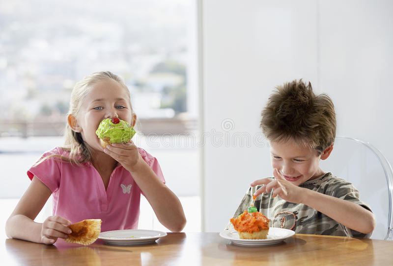 Szczęśliwi rodzeństwa Je filiżankę Zasychają Przy Łomotać stół obraz royalty free