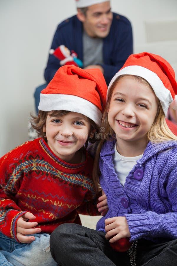 Szczęśliwi rodzeństwa Jest ubranym Santa kapelusze W Domu zdjęcia stock
