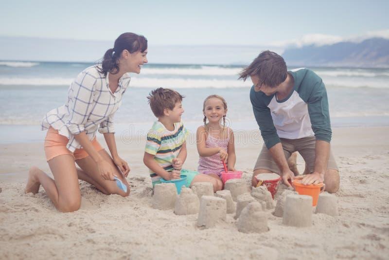 Szczęśliwi rodzeństwa z rodzicami robi piaskowi roszować zdjęcie royalty free