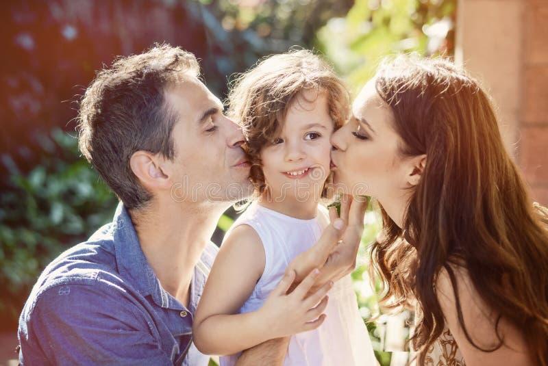 Szczęśliwi rodzice całuje ich ukochanego dziecka zdjęcia royalty free