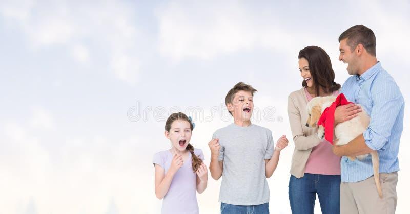 Szczęśliwi rodzice gifting szczeniaka dzieci przeciw niebu zdjęcie royalty free
