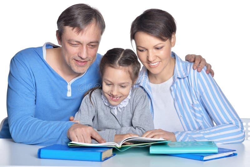 Szcz??liwi rodzice i c?rka robi pracie domowej na bia?ym tle obraz stock