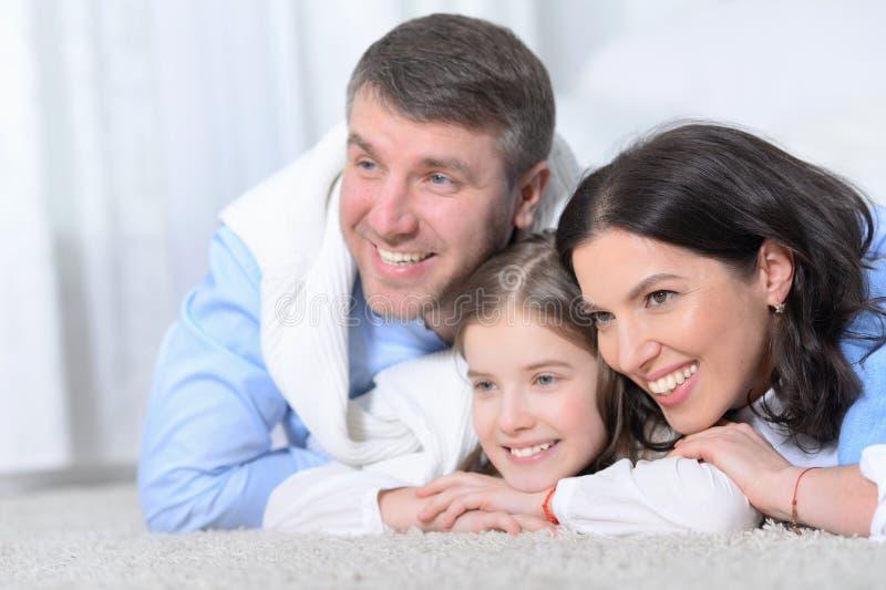 Szczęśliwi rodzice i córki lying on the beach na podłodze w pokoju obraz stock