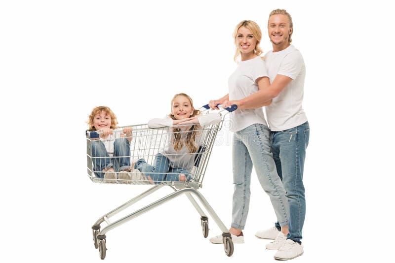 szczęśliwi rodzice i dzieciaki w wózek na zakupy zdjęcia stock