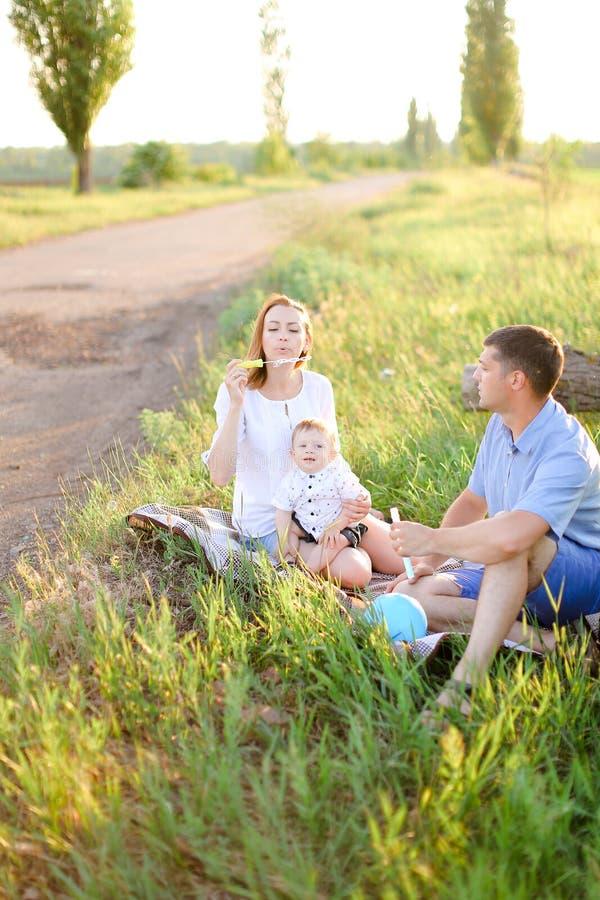 Szczęśliwi rodzice siedzi na trawie z małego dziecka i dmuchania bąblami fotografia royalty free