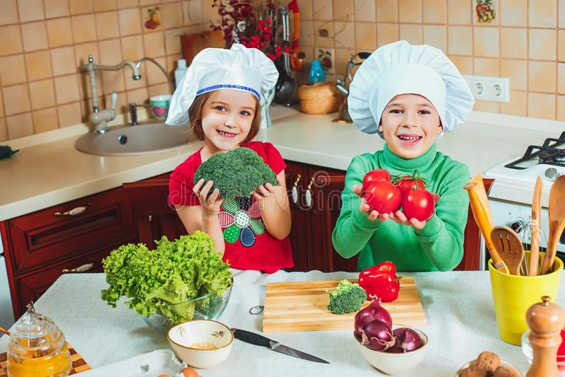 Szczęśliwi rodzinni śmieszni dzieciaki przygotowywają świeżego warzywa sałatki w kuchni obraz stock