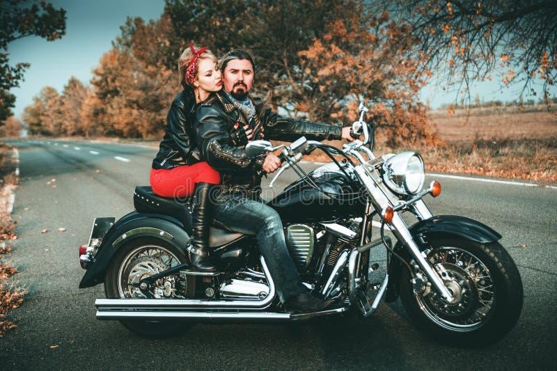 Szczęśliwi rowerzyści pozuje z motocyklem zdjęcia stock