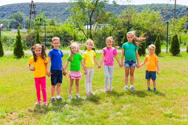 Szczęśliwi rozochoceni dzieciaki w kolorowych koszulkach fotografia royalty free