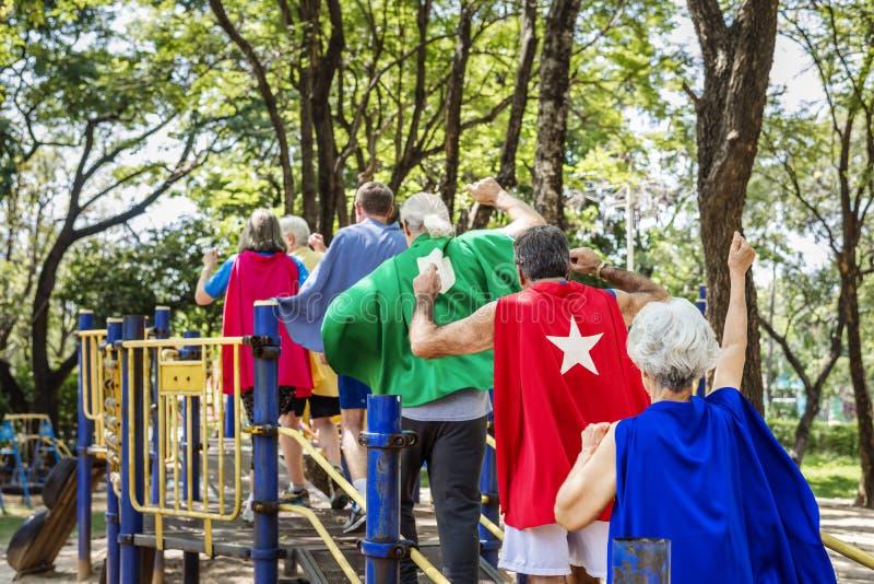 Szczęśliwi seniory jest ubranym bohaterów kostiumy przy boiskiem fotografia stock