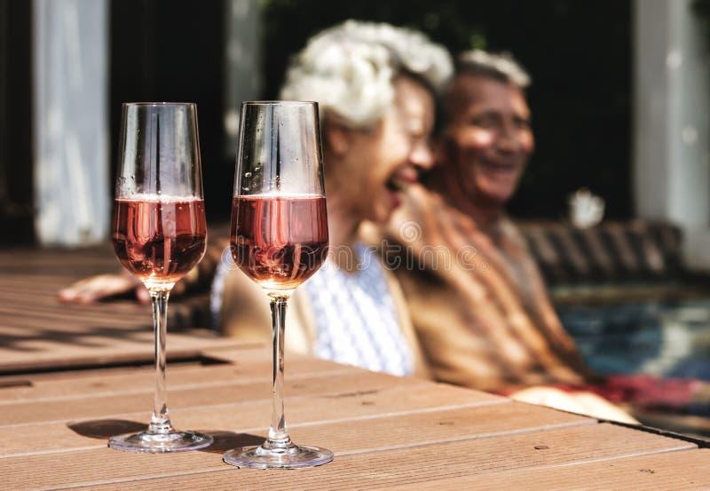 Szczęśliwi seniory pije prosecco w basenie obraz stock