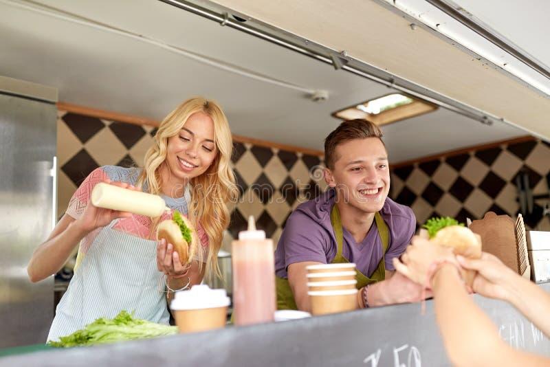 Szczęśliwi sprzedawcy słuzyć klientów przy jedzenie ciężarówką zdjęcia royalty free
