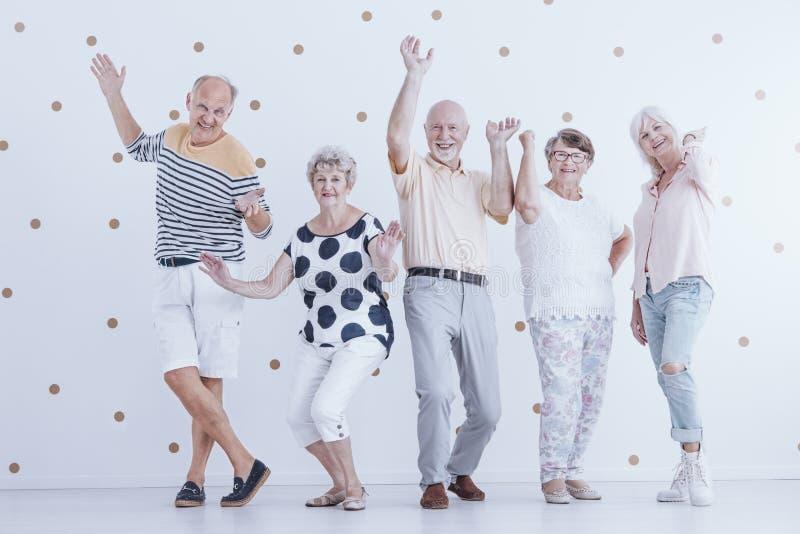 Szczęśliwi starsi ludzie tanczy przeciw białemu tłu z złocistym d fotografia stock