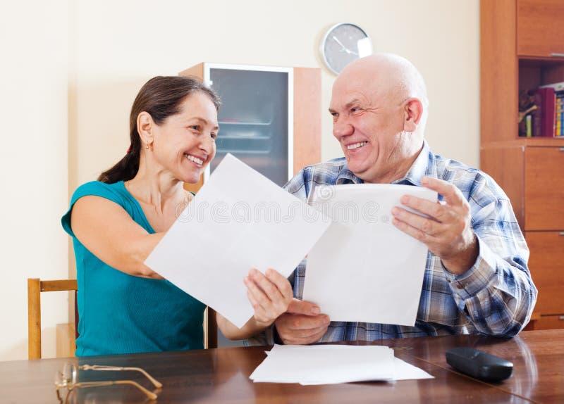 Szczęśliwi starsi pary mienia dokumenty w domu zdjęcia royalty free