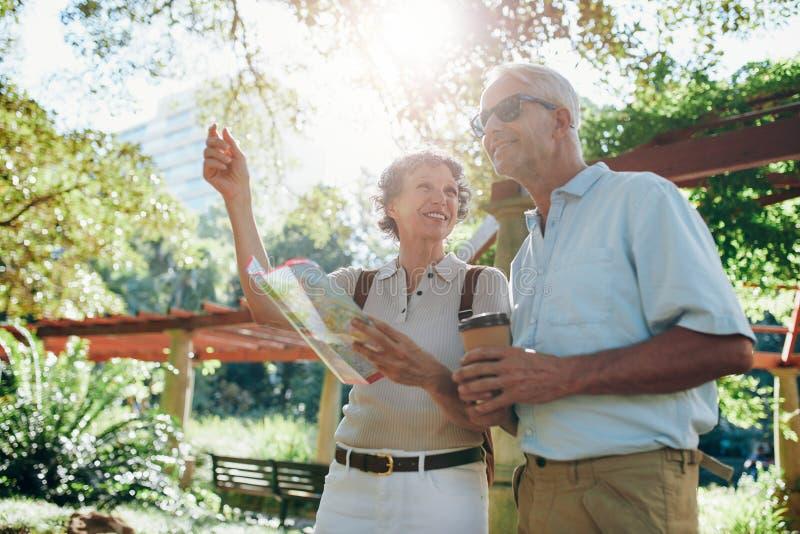 Szczęśliwi starsi turyści czyta mapę zdjęcie stock