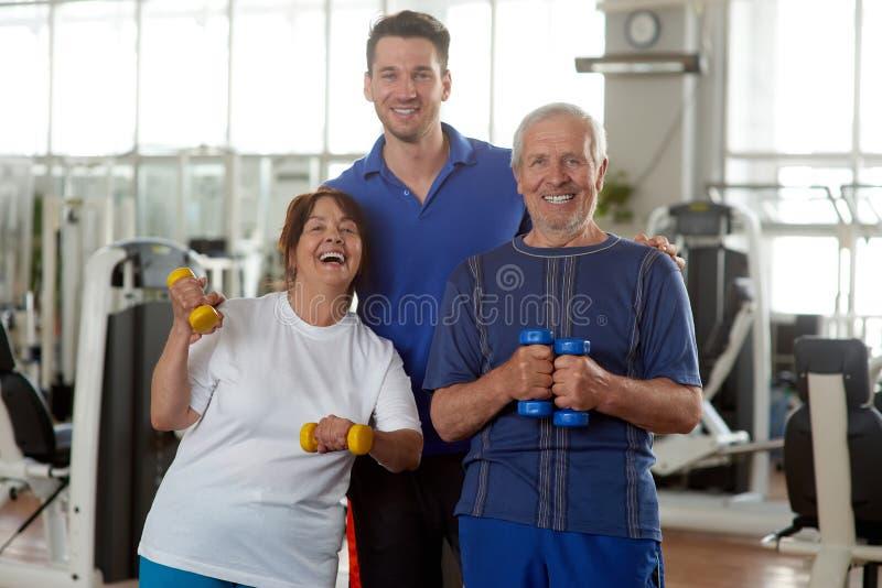 Szczęśliwi starszy ludzie z osobistym sprawność fizyczna trenerem fotografia royalty free