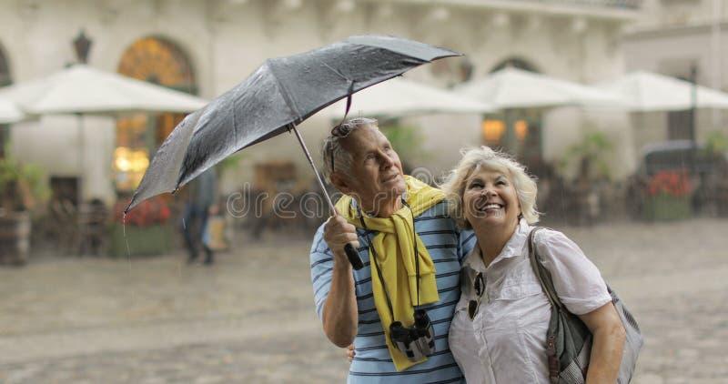 Szczęśliwi starszy turyści stoją śródmieście i cieszą się dżdżystą pogodę w Lviv zdjęcie stock