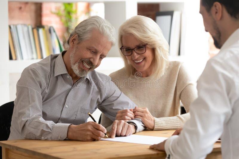 Szczęśliwi starzy para klienci podpisują asekuracyjnego kontrakta spotkania agenta obraz stock