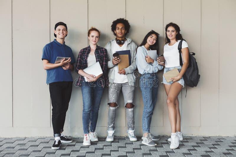 Szcz??liwi student collegu pozuje z studiowanie personelem przy kampus ?cian? obraz royalty free