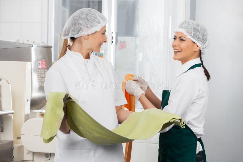 Szczęśliwi szefowie kuchni Conversing Ciąć na arkusze Podczas gdy Trzymający makaron zdjęcia royalty free
