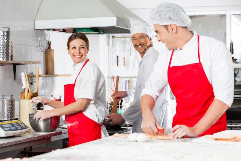 Szczęśliwi szefowie kuchni Conversing W Handlowej kuchni obrazy stock
