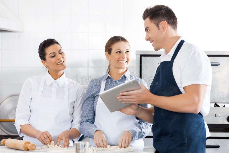 Szczęśliwi szefowie kuchni Dyskutuje przepis Na Cyfrowej pastylce Wewnątrz zdjęcie stock