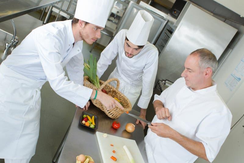 Szczęśliwi szefowie kuchni pracuje w kuchni obraz royalty free