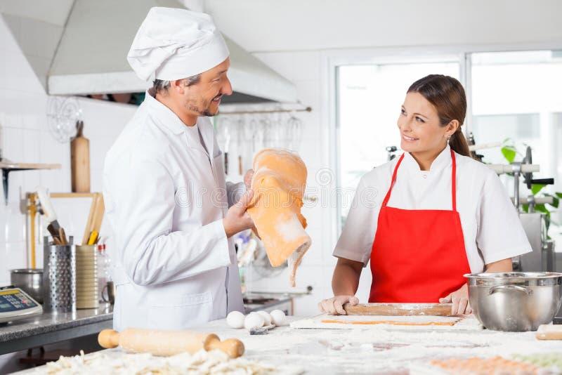 Szczęśliwi szefowie kuchni Przygotowywa makaron Przy Kuchennym kontuarem zdjęcia stock