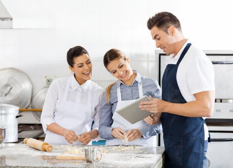 Szczęśliwi szefowie kuchni Sprawdza przepis Na Cyfrowej pastylce Wewnątrz obraz stock