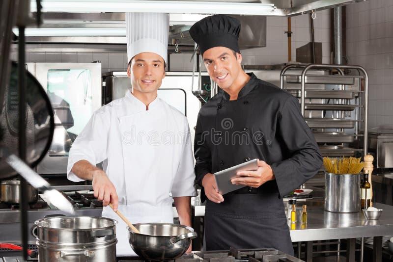 Szczęśliwi szefowie kuchni Z Cyfrowej pastylki Kulinarnym jedzeniem obraz royalty free