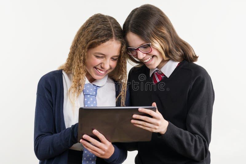 Szczęśliwi szkoła średnia przyjaciele są nastoletnimi dziewczynami, patrzeją pastylkę i emocjonalnie reagują, obraz royalty free